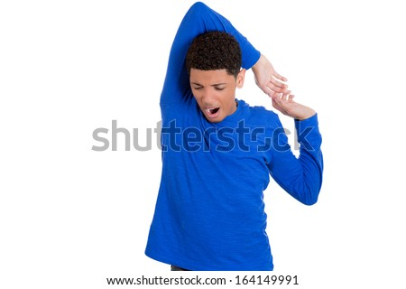 Closeup portrait of handsome tired fatigued man in blue shirt stretching arms, back, shoulders and hands, isolated on white background with space to left. Positive human emotion facial expression - stock photo