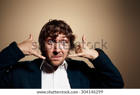 Closeup portrait of handsome young business man looking at camera and gesturing mobile phone near his face while standing against gold background. Positive human emotion, facial expression sign symbol - stock photo