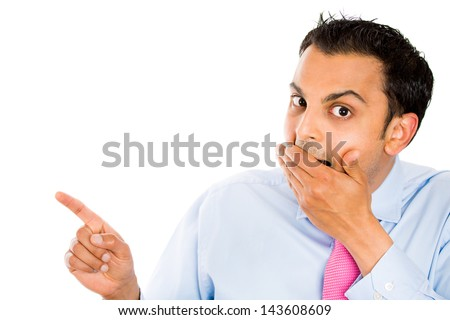 Closeup portrait of handsome young businessman covering his mouth, laughing, and pointing at someone or something and looking at you, with copy space, isolated on white background - stock photo