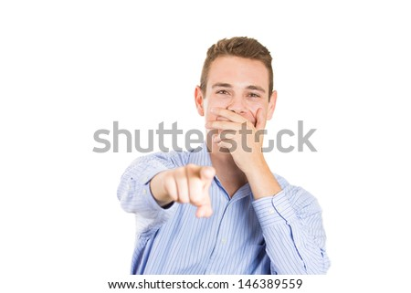 Closeup portrait of handsome young businessman covering his mouth, laughing, and pointing at someone or something, with copy space, isolated on white background - stock photo