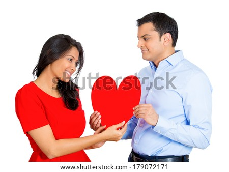 Closeup portrait of handsome young man happily giving red heart to pretty beautiful surprised woman, isolated on white background. Positive emotion facial expression feelings.Puppy love is in the air. - stock photo