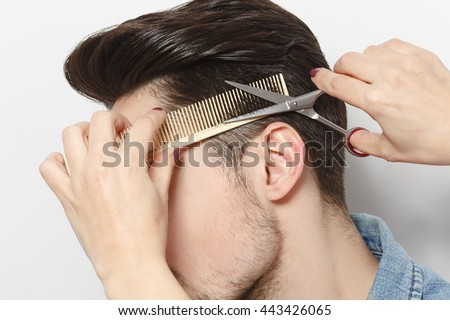 Closeup portrait of handsome young man having haircut in studio. Hairdresser cutting man'shair with scissors over white background. - stock photo