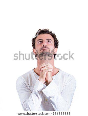 Closeup portrait of handsome young man praying for help or forgiveness, isolated on white background with copy space