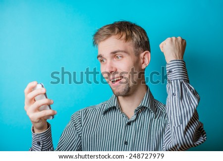 Closeup portrait of handsome young man, shocked surprised guy, opened mouth, eyes, by what he sees on his cell phone. - stock photo