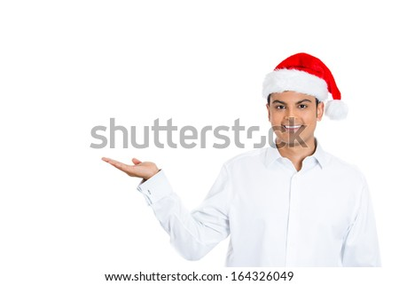 Closeup portrait of handsome young man wearing red santa claus hat gesturing with hand palm up, space to left, isolated on white background. Positive human emotion facial expression. - stock photo