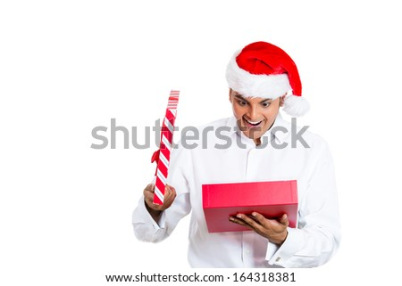 Closeup portrait of handsome young man wearing red santa claus hat, shirt, opening gift and happy at what he gets, isolated on white background, space to left. Positive emotion facial expression - stock photo