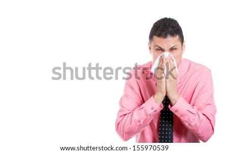 Closeup portrait of handsome young man with allergy or cold, blowing his nose, looking miserable and very sick, isolated on white background with copy space. Flu season and vaccination.  - stock photo