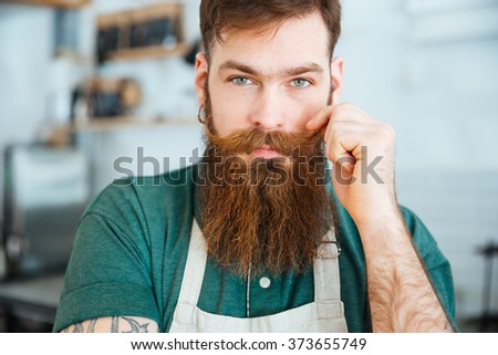 Closeup portrait of handsome young man with beard in white apron touching his moustache - stock photo