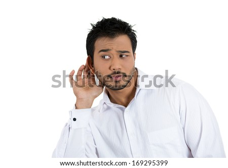 Closeup portrait of handsome young nosy man trying to secretly listen in on a conversation, hand to ear surprised excited at juicy gossip he hears, privacy violation, isolated on white background