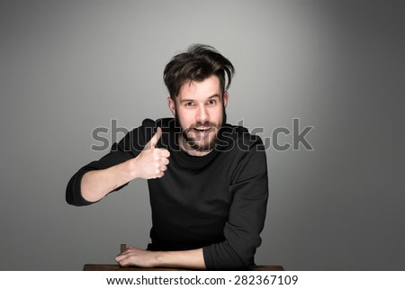 Closeup portrait of handsome young smiling man, giving a raised finger on gray background. Positive human emotions - stock photo