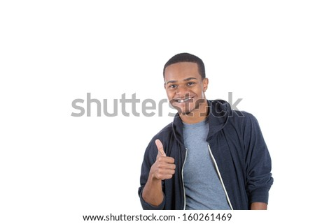 Closeup portrait of handsome young smiling man in black hoody giving one thumbs up at camera sign isolated on white background with copy space. Positive human emotions and signs. - stock photo