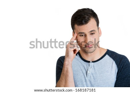 Closeup portrait of handsome young worried man thinking deeply, with finger on temple looking down, isolated on background with copy space to left. Human face expressions, emotions, feelings, attitude