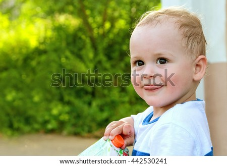 closeup portrait of happy adorable baby boy smiles outdoors. with copy space - stock photo