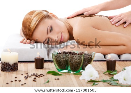 closeup portrait of happy beautiful young woman getting back massage with coffee scrub at spa