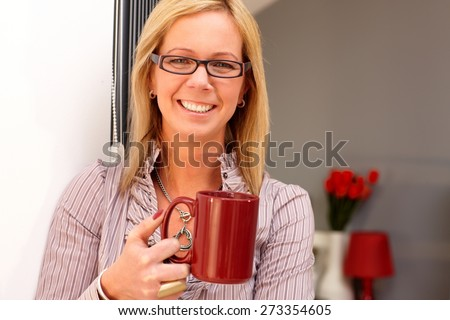 Closeup portrait of happy blonde woman holding tea mug, smiling, looking at camera. - stock photo