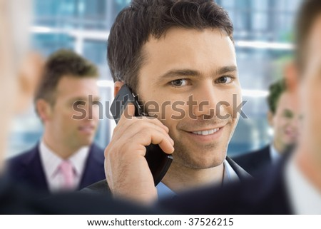 Closeup portrait of happy businessman talking on mobile in crowd in office lobby. - stock photo