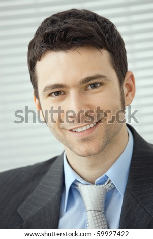 Closeup portrait of happy businessman wearing grey suit and blue shirt, looking at camera, smiling. - stock photo