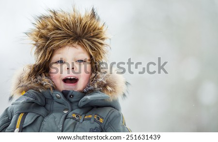 Closeup portrait of happy child in winter hat - stock photo