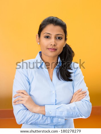 Closeup portrait of happy confident successful pretty young woman in blue shirt with arms crossed, isolated on orange, red background. Positive human emotions, facial expressions, feelings, attitude