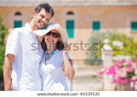 Closeup portrait of happy couple standing in front of the villa. Mallorca. Spain - stock photo