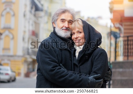 Closeup portrait of happy elderly couple wearing coats embracing on street  - stock photo