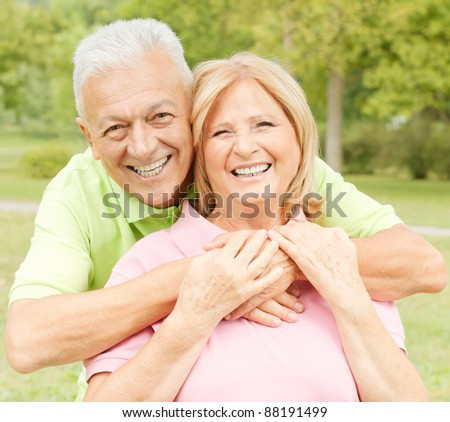 Closeup portrait of happy elderly man embracing mature woman.