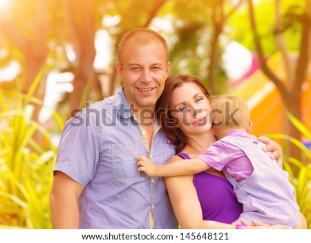 Closeup portrait of happy family in the park, mother carry little baby boy, parents with cute child enjoying warm sunny day, love and happiness concept