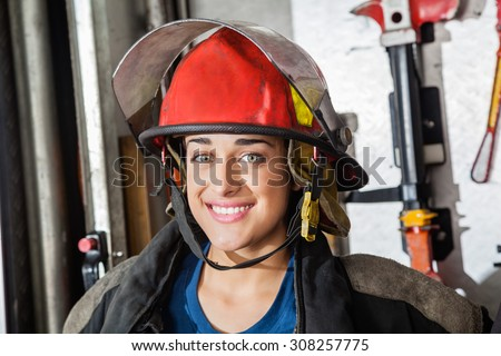 Closeup portrait of happy female firefighter at fire station - stock photo