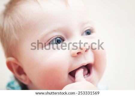 Closeup portrait of happy funny baby with finger in the mouth, adorable sweet child with beautiful grey eyes, healthy childhood - stock photo