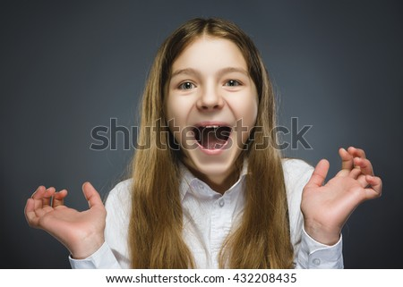 Closeup Portrait of happy girl going surprise isolated on gray background