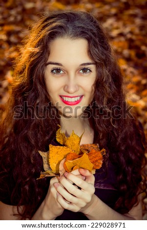 Closeup portrait of happy girl in the autumn park - stock photo