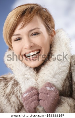 Closeup portrait of happy, laughing young woman wearing fur coat - stock photo