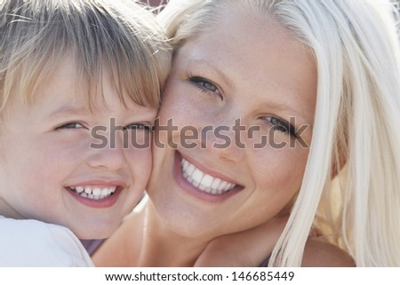 Closeup portrait of happy little boy and mother cheek to cheek - stock photo