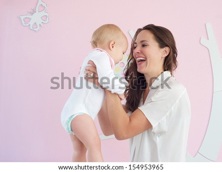Closeup portrait of happy mother holding cute baby at home