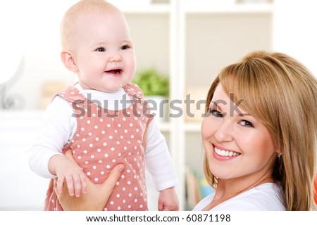 Closeup portrait of  happy mother with newborn baby - indoors - stock photo