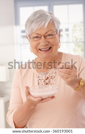 Closeup portrait of happy old lady eating breakfast cereal, smiling, looking at camera. - stock photo
