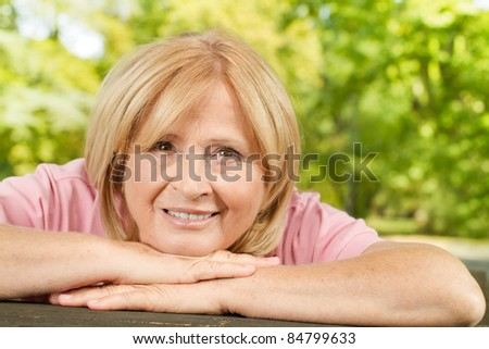 Closeup portrait of happy old woman outdoors. - stock photo