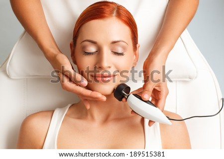 closeup portrait of happy redheaded woman with closed eyes getting rf-lifting in a beauty salon