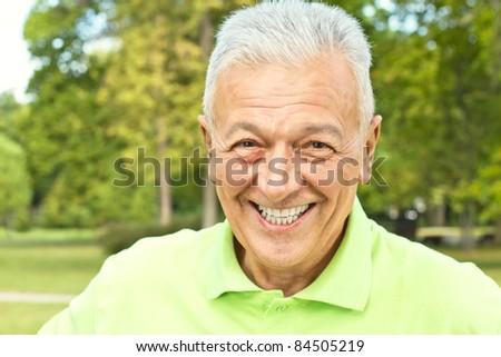 Closeup portrait of happy senior man outdoors. - stock photo