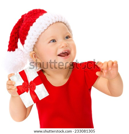 Closeup portrait of happy smiling child with Christmas gift isolated on white background, wearing red Santa hat for Xmas celebration  - stock photo