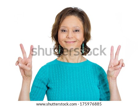 Closeup portrait of happy smiling senior mature confident woman giving peace victory or two sign gesture, isolated on white background. Positive emotion facial expression feelings symbols, attitude