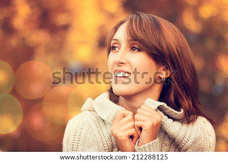 Closeup Portrait of Happy Smiling Woman in Cozy Sweater on Autumn Nature Background. Toned Photo. Shallow Depth of Field. Copy Space. - stock photo