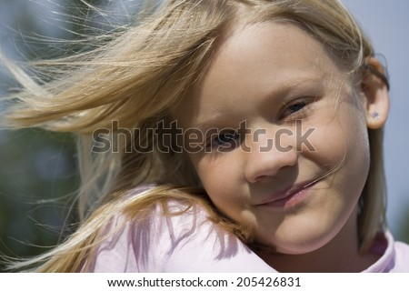 Closeup portrait of happy smiling young scandinavian girl outdoors on sunny summer day with wind blowing hair