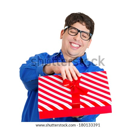 Closeup portrait of happy super excited young man with glasses about to open unwrap red gift box isolated on white background, enjoying his present. Positive emotion facial expression feeling attitude