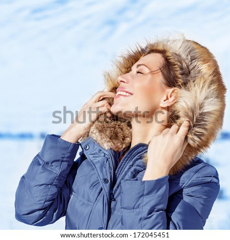 Closeup portrait of happy woman with closed eyes enjoying sun light in cold frosty day, wearing fashionable wintertime clothes, luxury model in snowy park - stock photo