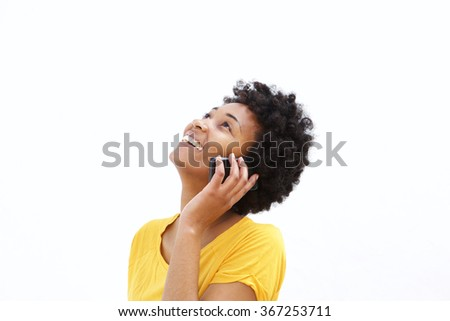 Closeup portrait of happy young african woman talking on mobile phone and looking up while standing against white background  - stock photo