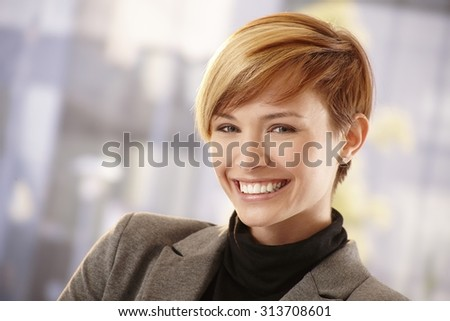 Closeup portrait of happy young businesswoman in spring sunshine, smiling - stock photo