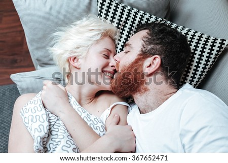 Closeup portrait of happy young couple in bed. - stock photo