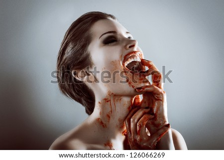 Closeup portrait of horror beautiful vampire woman with blood - stock photo