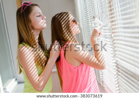 closeup portrait of hugging 2 beautiful blond young women having fun happy smiling and spying of window background - stock photo